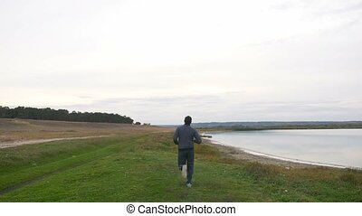 man runner athlete in a sports suit runs on the nature of the landscape
