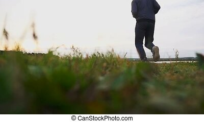 man runner athlete runs on nature near a lake healthy...