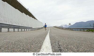 man runner leader of mountain marathon running motorcycle...