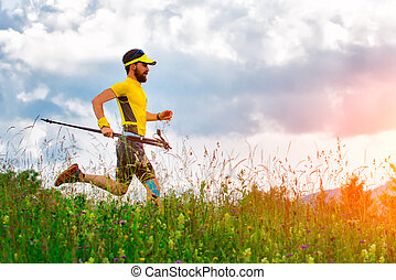 Man runner with rackets in hand down in the meadows