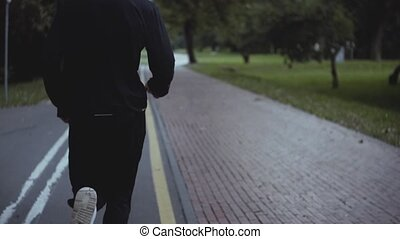 Man running along a park road. Slow motion. Back view....