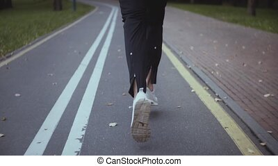 Man running along an autumn park road. Back view. Tilt up. Slow motion. Sportsman jogging on a peaceful quiet alley.