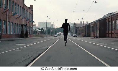 Man running along an old city district street. Back view. On...