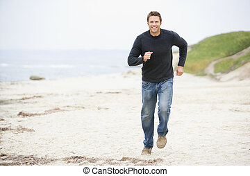 Man running at beach smiling