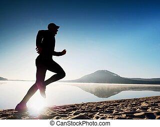 Man running at seaside twilight time. Runner athlete running at seaside. Sportsman fitness silhouette