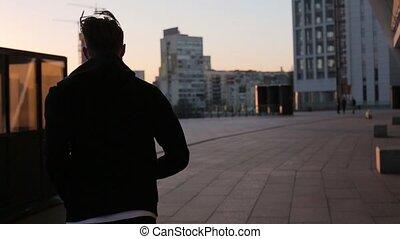 Man running at sunset in city