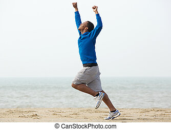 Man running at the beach with arms raised in victory