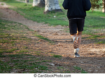Man running cross country on trail