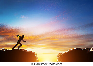 Man running fast to jump over precipice between two mountains. Challenge