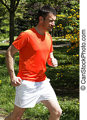 man running in a park in spring