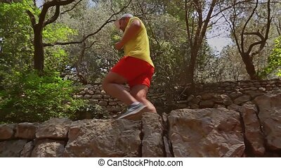 Man running in Mediterranean scenery, slow motion video