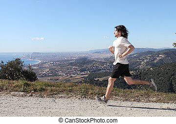 Man running in the mountain with a big city in the background
