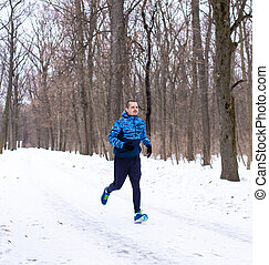 Man running in the winter forest with a lot of snow