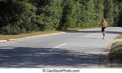 Man Running Marathon - Man in marathon race runs alone down...