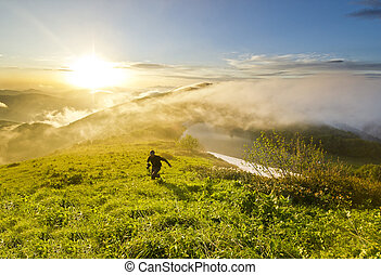 man running on a hill at sunset with camera