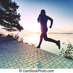 Man running on lake shore pavement during sunrise or sunset