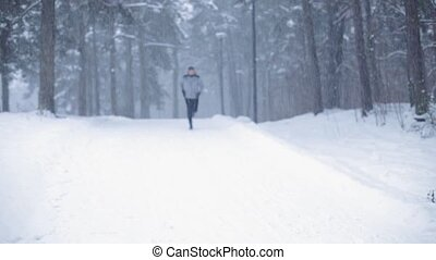man running on snow covered winter road in forest