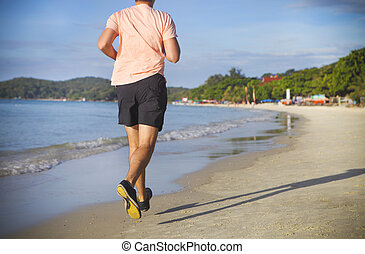 Man running on the beach at sunrise