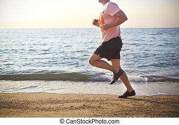 Man running on the beach at sunset