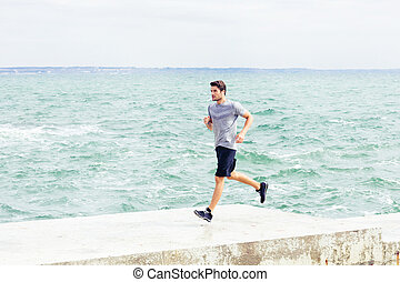 Man running on the pier at beach
