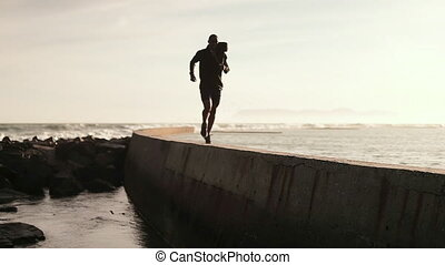 African American man wearing sports clothes, enjoying exercising at the beach, jogging on a sea wall, backlit, in slow motion