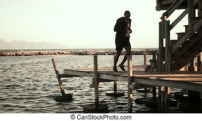 African American man wearing sports clothes, enjoying exercising on a sunny day at the beach, jogging on a wooden jetty in the sea, in slow motion