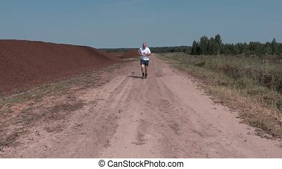 Man running on the rural road in summer