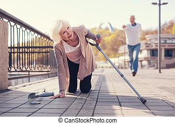 Man running to help senior woman get up