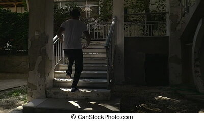 Man running up the steps of outdoor stairways in hotel