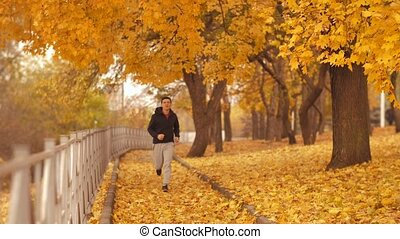 Man runs at autumn park