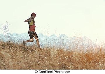 Man runs downhill among the autumn mountain meadows