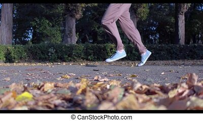 Man runs in green autumn forest lightened with sun - Healthy...