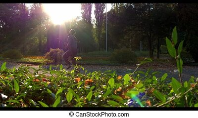 Man runs in green autumn forest lightened with sun