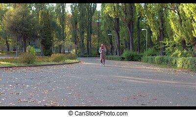 Man runs in green summer forest lightened with sun