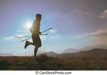 Man runs in the mountains with sticks in his hand