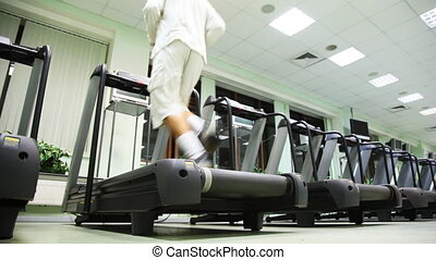 man runs on one of many treadmill in large empty gym