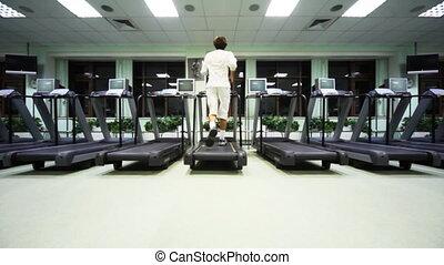 man runs on treadmill in large empty gym