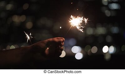 Man s hands holding a sparkler at night