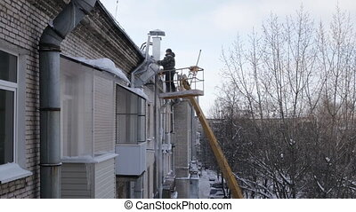 Man safely remove icicles from eaves