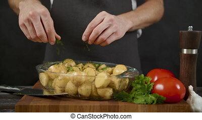 Man salt potato in the dark kitchen.