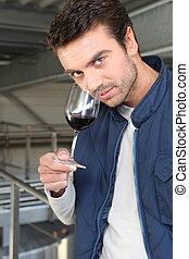 Man sampling wine production