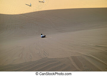 Man Sand Boarding Down the Sand Dune of Huacachina Desert, Ica Region of Peru, South America