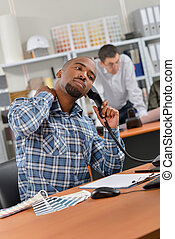 Man sat at desk, on telephone, stretching neck