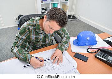 Man sat at desk working on blueprints