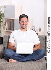 Man sat at home using laptop computer