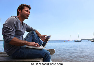 Man sat by lake
