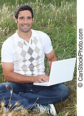 Man sat in field using laptop computer