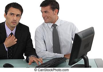 Man sat next to colleague adjusting tie