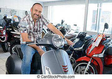 man sat on a modern scooter in a dealers showroom