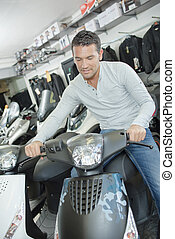 Man sat on modern scooter in showroom